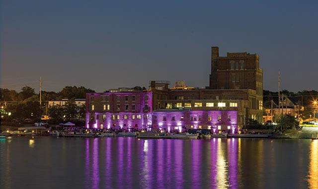A prime view of the Prairie Street Brewhouse and Marina along the Rock River lit up at night. (photo by C. Tyson Photography)