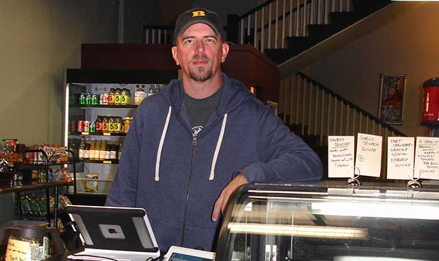 Darren Larsen, owner of Café Fromage, greets customers from behind a display case stocked with freshly baked breads, cookies and quiche.