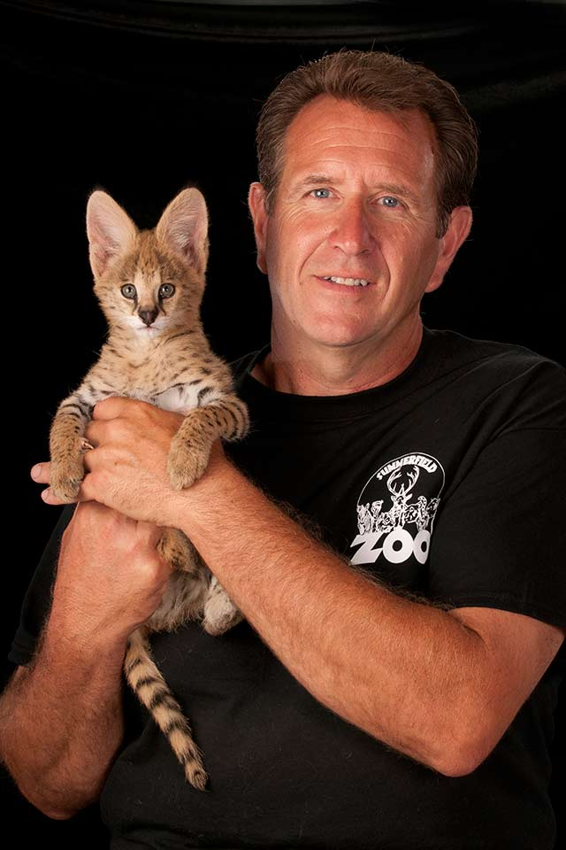 Zoo owner Rick Anderson holding Khan, an African serval.